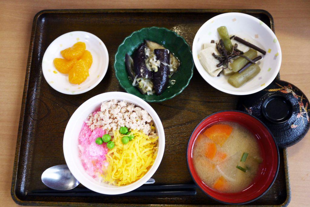 きょうのお昼ごはんは、3色丼・炊き合わせ・蒸しナスの薬味がけ・根菜汁・くだものでした。