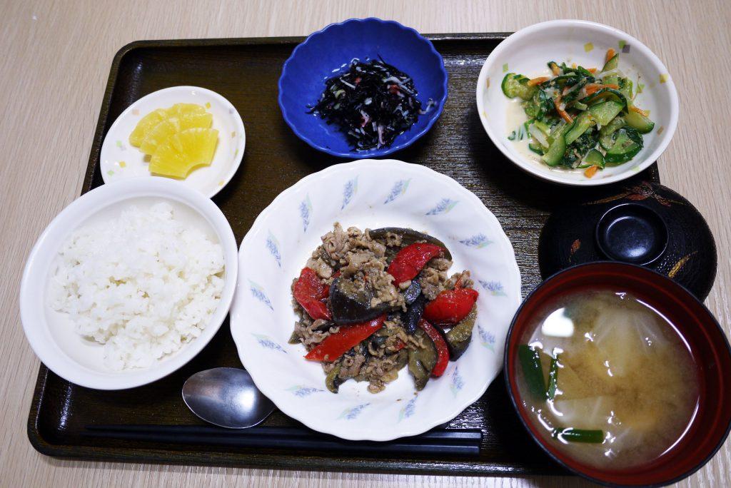 きょうのお昼ごはんは、なすと豚肉の鍋しぎ、青菜和え、ひじきの酢の物、みそ汁、果物でした。