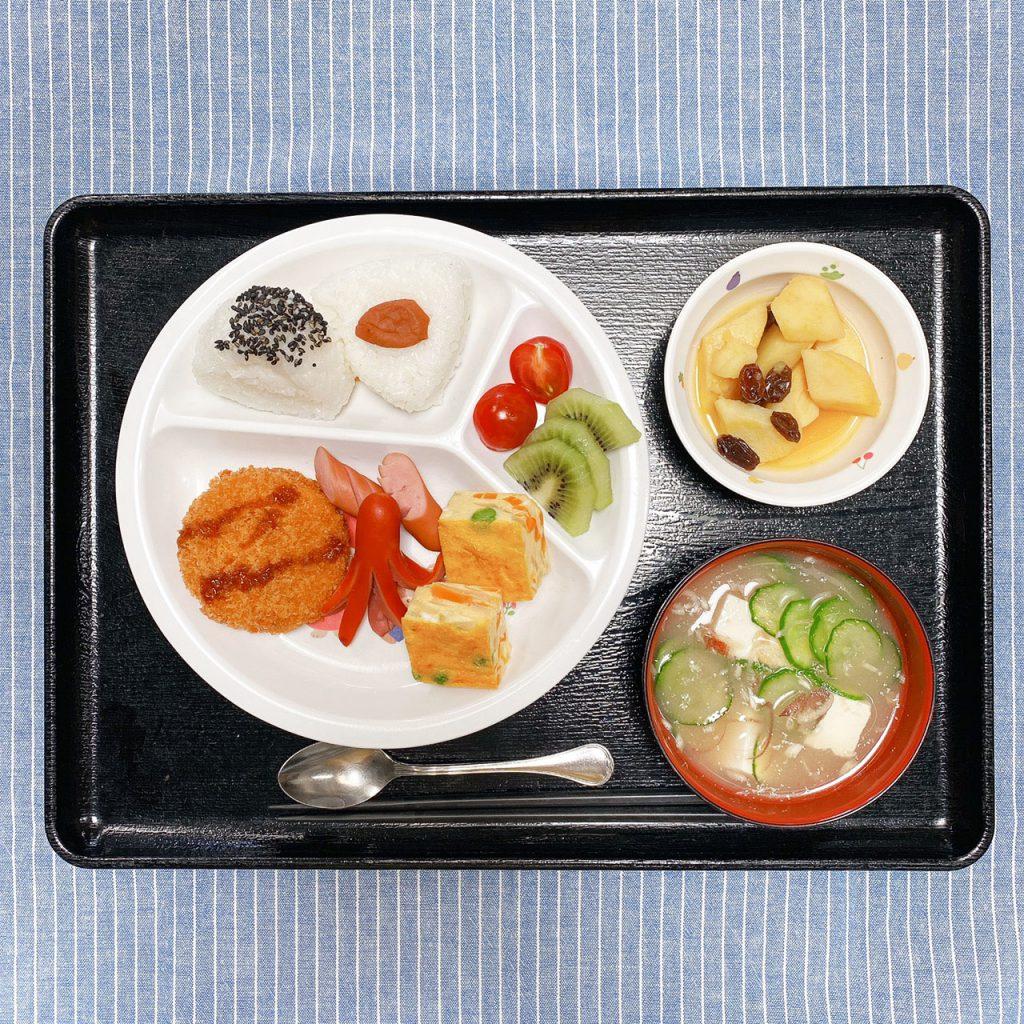 きょうのお昼ごはんは、お弁当風お楽しみ献立<おむすび(ゴマ塩・梅)、クリームコロッケ、卵焼き、ウインナー、さつまいものオレンジ煮、冷や汁、くだもの>でした。