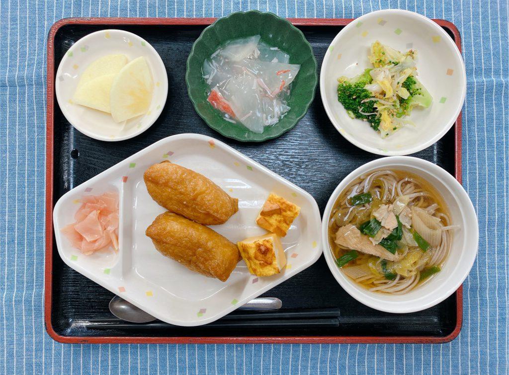きょうのお昼ごはんは、おそば・いなりずし・はんぺんのピカタ・青菜の旨味和え・くずあん・果物でした。